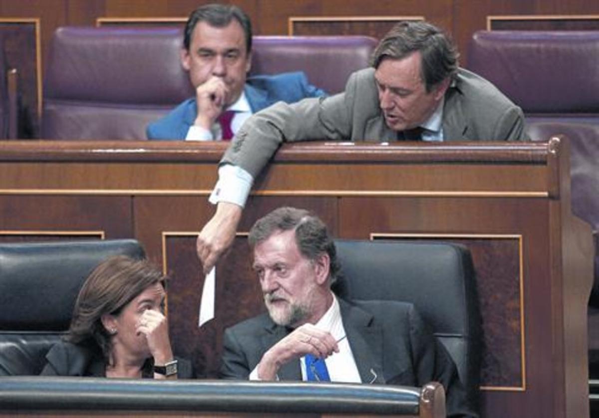 Mariano Rajoy y Soraya Sáenz de Santamaría hablan en el banco azul mientras Rafael Hernando les pasa una nota.