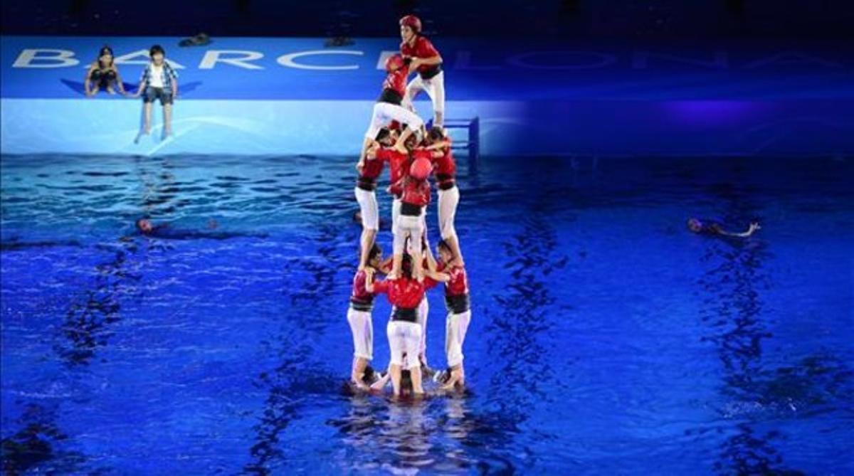 Los Castellers de Barcelona levantan un castillo en la piscina instalada en el Palau Sant Jordi, durante la inauguración de los Mundiales de natación.