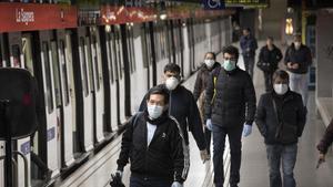 Viajeros con mascarilla en la estación de metro de la Sagrera.