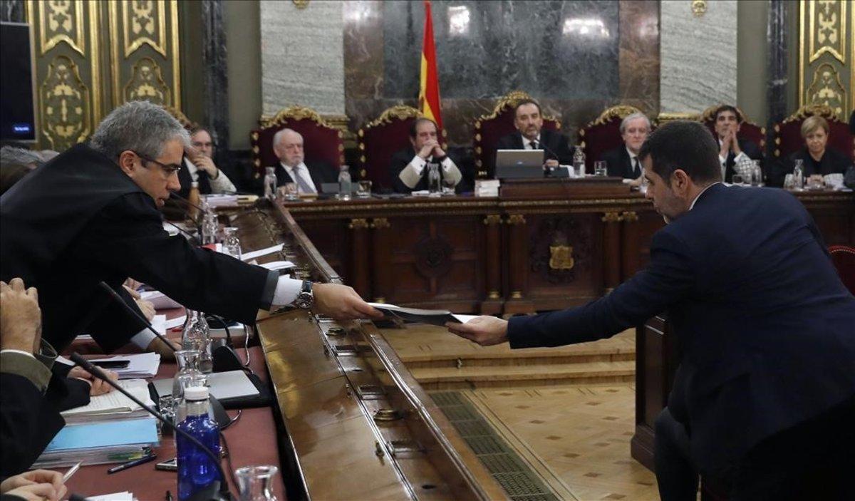 Francesc Homs intercambia un documento con Jordi Sánchez.