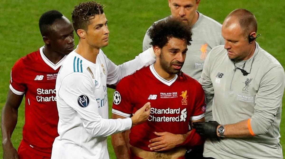 Salah abandona el estadio de Kiev tras la agresión de Ramos. Le consuela Cristiano.