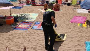 Un policía local retira toallas en la playa de Tamariu.