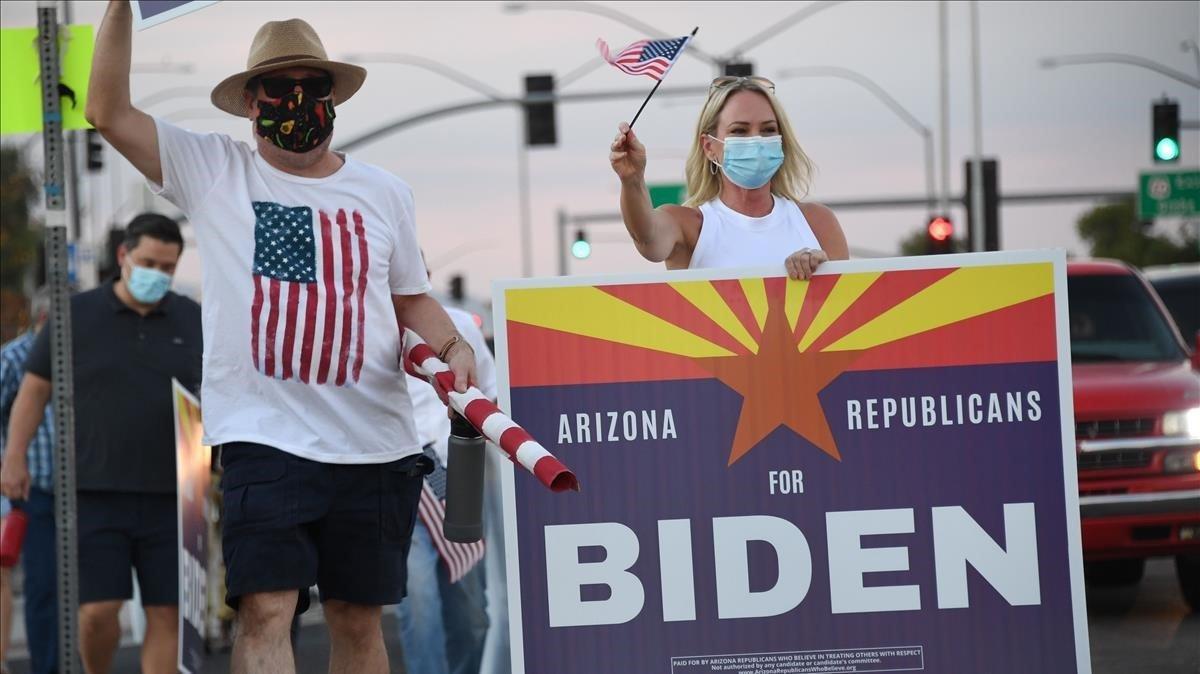 Miembros del grupo 'Republicanos de Arizona que creen en tratar a los otros con respeto' con un cartel en apoyo a Biden, este sábado en Phoenix.