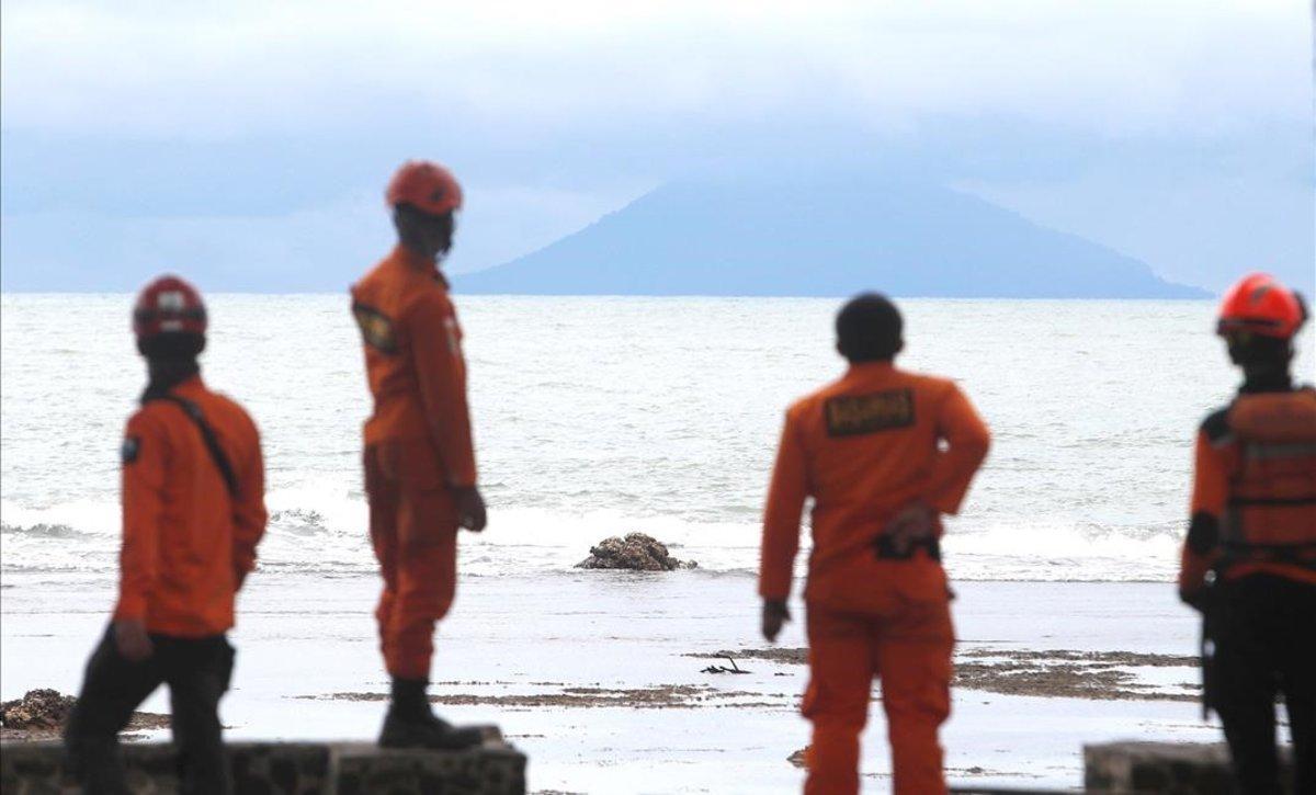 Miembros de los servicios de rescate observan la actividad del volcán Anak Krakatau desde la playa indonesia de Carita.
