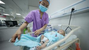 Una enfermera arropa a un bebé en el hospital de Danzhai, en la provincia china de Guizhou, este martes.