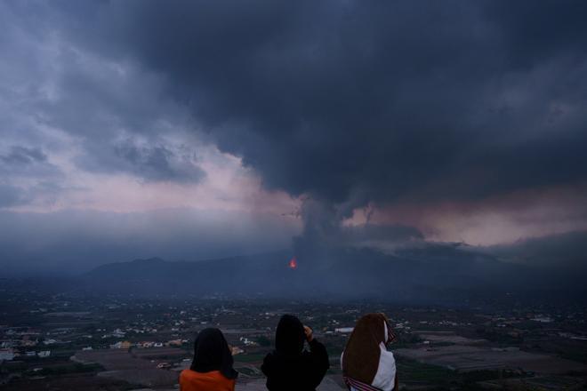 Unas niñas buscan con prismáticos su vivienda en el barrio de El Paraíso, una de las zonas más afectadas por la erupción que tiene lugar en la isla de La Palma.