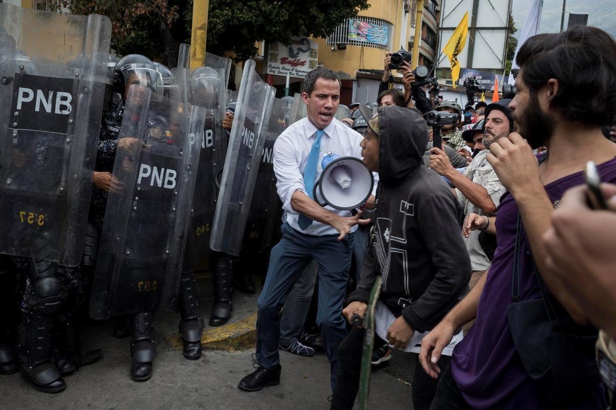 AME3191. CARACAS (VENEZUELA), 10/03/2020.- El líder opositor Juan Guaidó se une a simpatizantes durante los enfrentamientos con la Policía Nacional Bolivariana (PNB), este martes, en Caracas (Venezuela). La marcha había comenzado unos 30 minutos antes desde Chacao, un acomodado sector del este de Caracas y tradicional bastión opositor de la capital venezolana, y era la primera gran convocatoria de Guaidó desde que regresó de una gira internacional el pasado 11 de febrero. Al llegar a la zona, Guaidó cogió un megáfono y se metió entre los manifestantes y los policías, a quienes les dijo que en la marcha estaba la representación legítima del pueblo de Venezuela, en referencia a un nutrido grupo de diputados que intentaban llegar hasta el Palacio Legislativo para hacer la tradicional sesión de los martes. EFE/ Rayner Peña R.