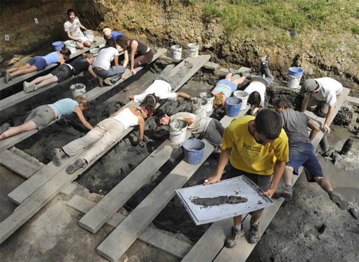 Un grupo de arqueólogos trabaja en las excavaciones del Parque Neolótico de la Draga, en Banyoles, donde se ha hallado el arco de caza neolítico más antiguo de Europa.