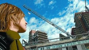 Una joven observa unas obras de construcción de pisos en Barcelona.