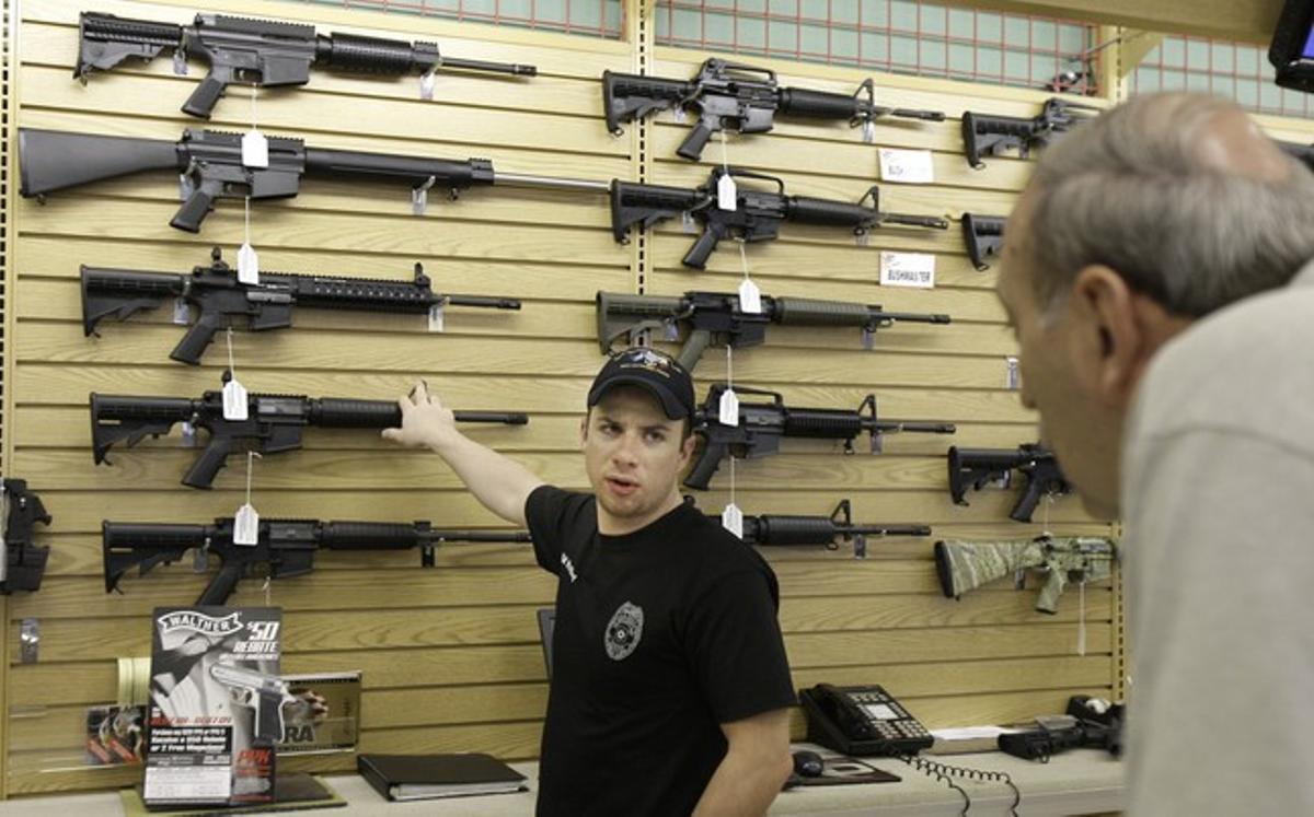 El dependiente de una tienda de armas de Fort Worth (Tejas) explica las características de un rifle a un cliente.