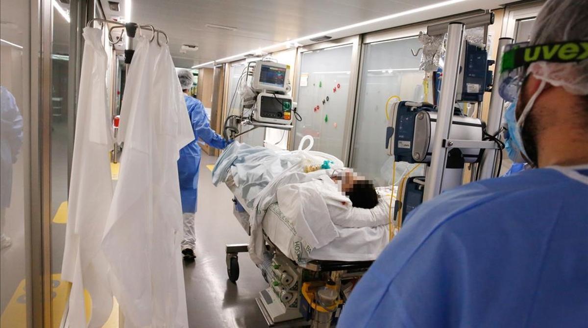 Unos enfermeros trasladan a un enfermo de covid a otras dependencias en el Hospital Clínic de Barcelona, el pasado 17 de diciembre.