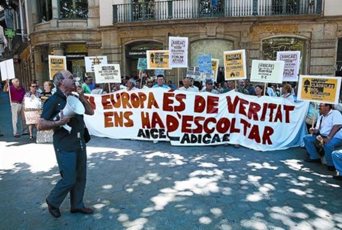 Concentración de afectados por preferentes y cláusulas suelo convocada por Adicae ante la sede de la UE en Barcelona.