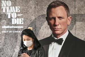 Una mujer con mascarilla ante un cartel de 'Sin tiempo para morir (No time to die') en Bangkok