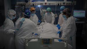Trabajadores sanitarios protegidos atienden a un paciente en la uci del Hospital del Mar, en Barcelona.