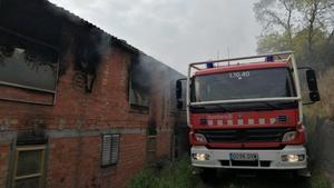 Un camión de Bomberos en el exterior de la granja incendiada de Castellbell i el Vilar
