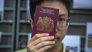 Un hongkonés posa con su pasaporte británico.