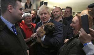 El primer ministro británico, Boris Johnson, sostiene un perro durante un encuentro conPaul Howell,el recién elegido diputado del Partido Conservador en Sedgefield, en el noreste de Inglaterra.