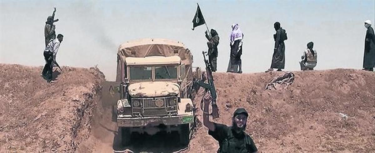 Un yihadista muestra su arma frente a un camión militar cerca de la frontera entre Irak y Siria.