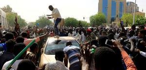Un grupo de manifestantes bloquea un coche del Ejército en Jartum.