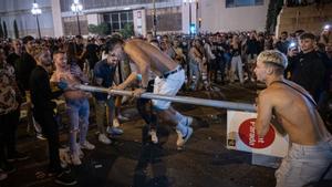 Unos jóvenes, el pasado sábado, destrozando mobiliario urbano en la avenida de Maria Cristina.