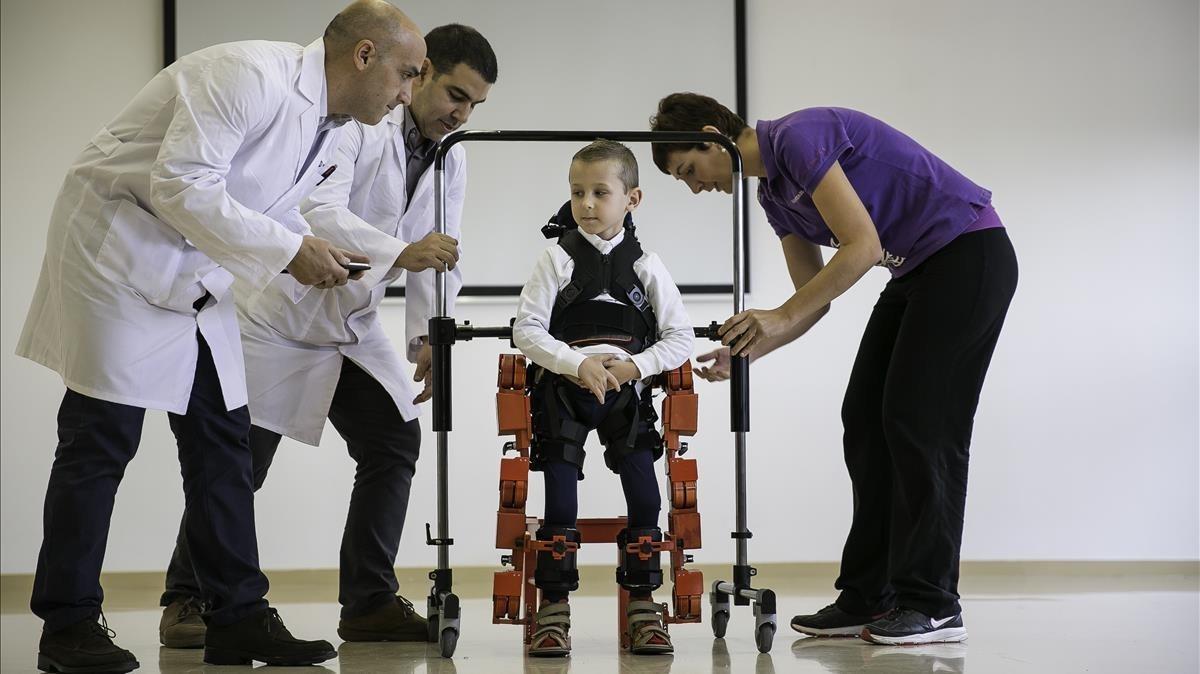 Médicos y fisioterapeutas del Hospital Sant Joan de Déu ayudan al pequeño Jens con el exoesqueleto.