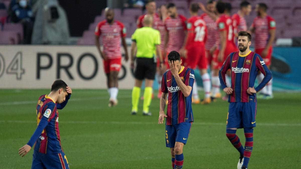 Pedri, Busquets y Piqué, desolados mientras los jugadores del Granada festejan el segundo gol.