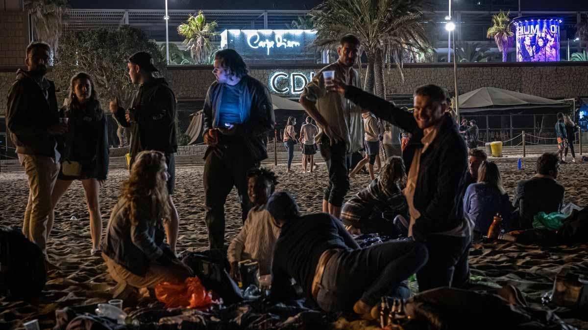 Unos jóvenes beben en la playa, frente a una zona de discotecas, en Barcelona.