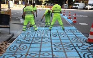 Operarios pintan la calle de Rocafort el mes pasado.