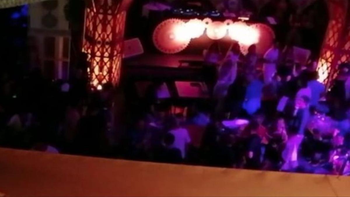 Imagen del interior del restaurante denunciado en el que se ve a varios clientes de pie bailando.