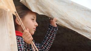 Lara, una niña siria de 7 años, mirando fuera de la tienda donde vive en un campo de desplazados en la zona rural de Idlib, noroeste de Siria.