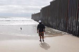 Migrante en el muro de separación con EEUU