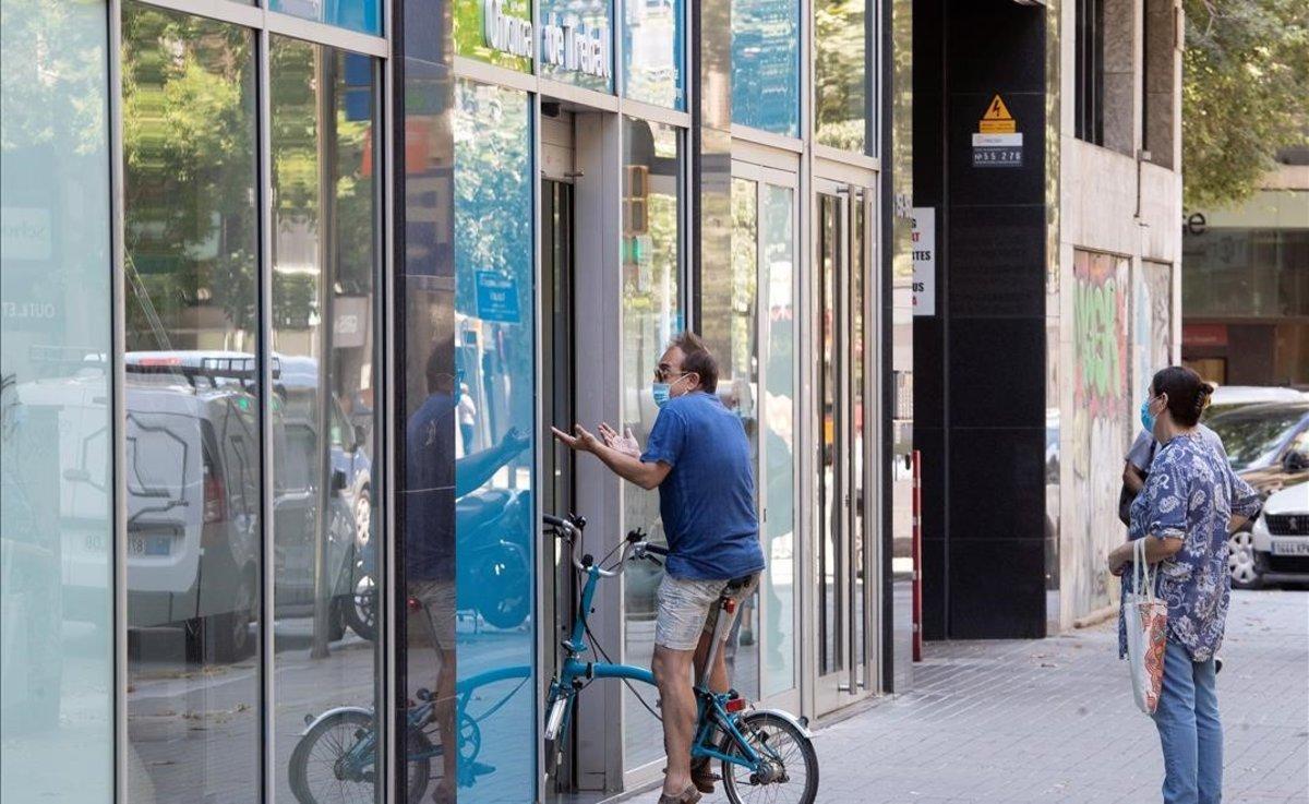 Dos personas hacen cola en una oficina de empleo de Barcelona, a principios de julio.