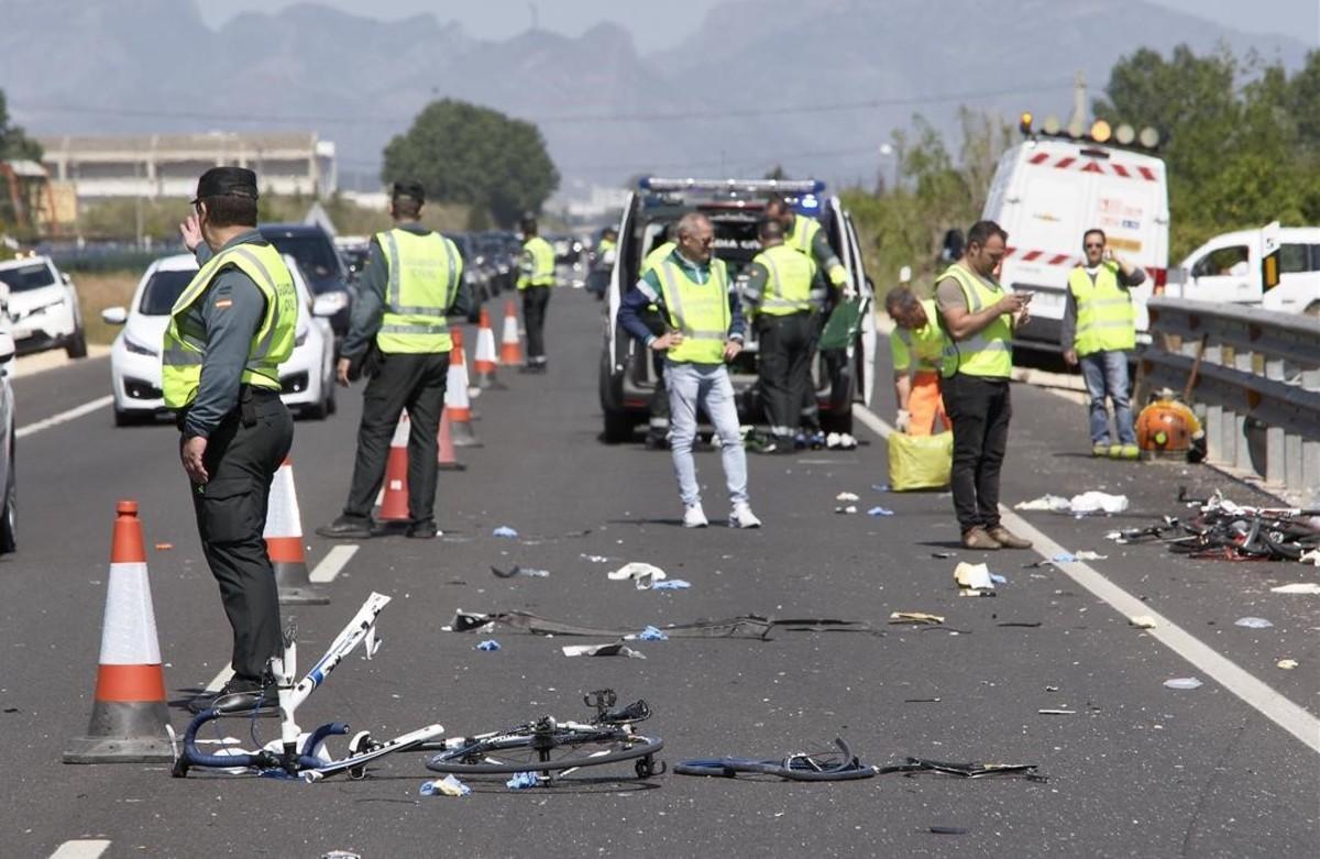 Agentes de la Guardia Civil y miembros de Emergencias, en el lugar en el que fallecieron dos ciclistas atropellados, en Oliva (Valencia).