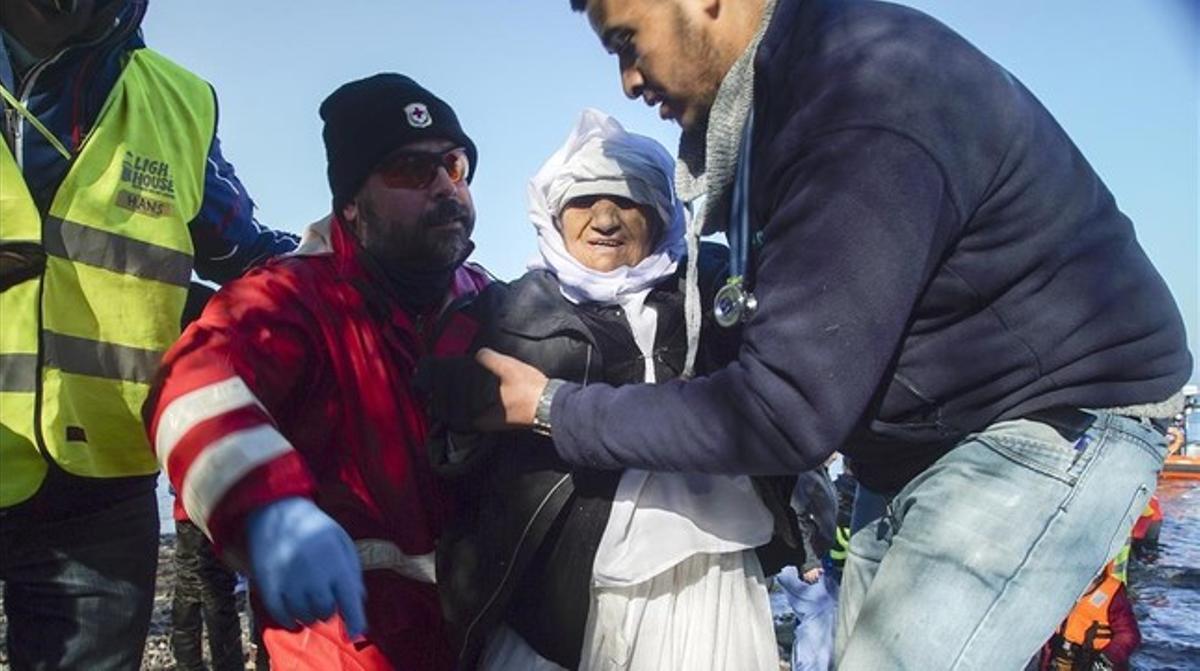 Voluntarios ayudan a una mujer anciana de Afganistán tras desembarcar con otros refugiados en Skala Sykaminias, en Lesbos, este miércoles.
