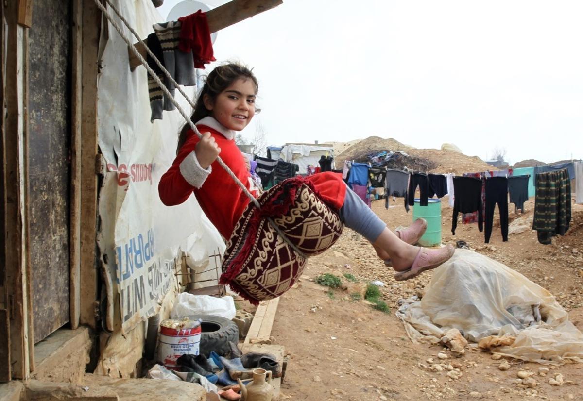 Una niña siria se columpia en un campamento de refugiados.